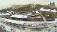 Train arrives to railway station at winter day. Aerial view Stock Footage