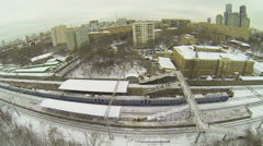 Train departs from railway station at winter day. Aerial view Stock Footage