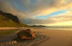 rock on beach lit by the norwegian midnight sun - stock photo