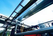Stock Photo of Industrial zone, Steel pipelines and valves against blue sky
