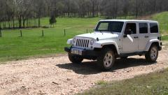Track and zoom in of white Jeep coming up gravel road - stock footage