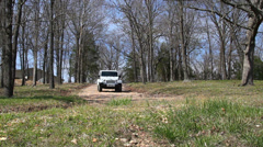 White Jeep coming down hill headed to lake Stock Footage
