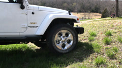 White Jeep going up over ditch Stock Footage