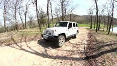 2014 White Jeep coming up gravel road Stock Footage