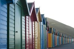 row of colorful wooden beach huts - stock photo