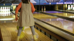 bowling - a little girl knocks down pins and very glad - stock footage