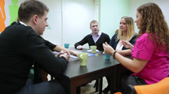 Young people talking together when playing guessing game at co-working space Stock Footage
