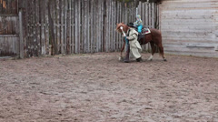 Cowboy leading a horse by the bridle with sitting little child Stock Footage