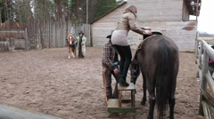 Young woman sitting on the horse for riding in paddock. Country ranch Stock Footage
