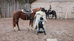 Cowboy sitting little girl on the horseback for riding around paddock, ranch Stock Footage