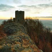 The stony ruin of medieval stronghold on the peak of rocky hill. Stock Photos