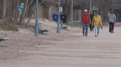 People walking on the board walk and beach on cool day Stock Footage