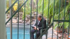 Businessman Enters And Sits Through Bars Stock Footage
