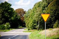 Yield sign near crossroad Stock Photos