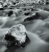 Stock Photo of Night winter view to icicles and icy boulders into the stream.