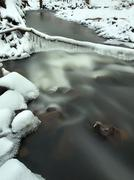 Night winter view to icicles and icy boulders into the stream. - stock photo