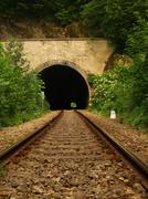 View into old railway tunnel, rusty rails and oiled sleepers - stock photo