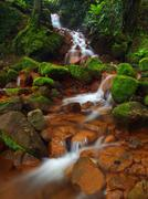 Cascades in rapid stream of mineral water. Red ferric sediments on big boulders Stock Photos