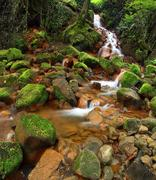 Cascades in rapid stream of mineral water. Red ferric sediments on big boulders - stock photo