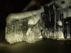 Night winter view to icicles and icy boulders into the stream - stock photo