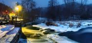Stock Photo of Winter night below weir. Reflection of lamps in icicle, ice and cold water