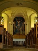 Interieur of common village church, wooden crucifix, statues, wooden benches Stock Photos