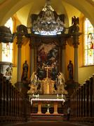 Interieur of rich village church, wooden crucifix, statues, wooden benches Stock Photos