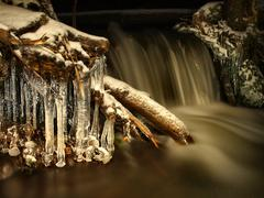 Stock Photo of Night winter view to icicles, icy branches and boulders into chilling stream.