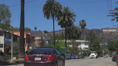 Hollywood sign letter traffic car street road palm tree house landmark iconic US - stock footage