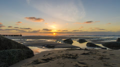 Sunset time lapse over a rocky, sandy beach -  24 FPS timelapse  Stock Footage
