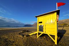 Water lifeguard chair cabin red flag   rock stone sky Stock Photos