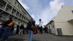 2 angles - tourist walk past Alcatraz watch tower 2 Stock Footage
