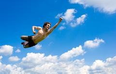 The crazy flying man in clouds Stock Photos