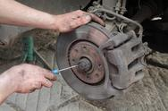 Stock Photo of car mechanic works on disc brakes with tool