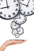 hand holding phone with analog clocks - stock illustration