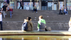 Couple sitting on the edge of fountain in front of big stairs - blurred crowd Stock Footage
