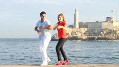 Cuban young Couple dancing salsa in Havana with Morro Castle in Back Ground Stock Footage