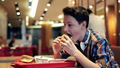 Young teenager eating tasty hamburger in fast food restaurant HD - stock footage