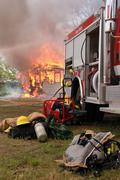 Fire Truck and Turnout Gear with Burning House in Back Stock Photos