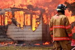 Fire Fighter Looks on as House Burns - stock photo