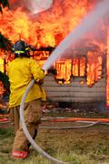 FIre Fighter Spraying House Fire With Water Hose - stock photo