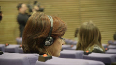 Journalist with headphones at press conference - stock footage