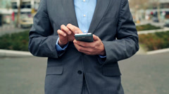 Businessman hands texting on smartphone in the city HD Stock Footage
