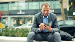 Businessman texting, sending sms on smartphone in the city HD Stock Footage