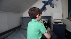 Kid playing with a plush toy, very happy child, boy in his room, back view Stock Footage