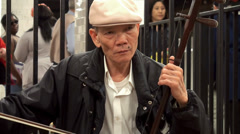 Chinese man street performer playing Erhu music at the NYC subway. Stock Footage
