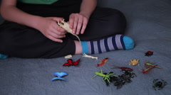 Boy's hands playing in bed with insect toys, child having fun in his room Stock Footage