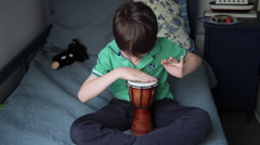 Little boy sitting in bed, kid playing to drum, child, hand drummer, tambourine - stock footage