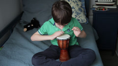 Little boy sitting in bed, kid playing to drum, child, hand drummer, slow motion - stock footage