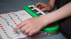 Child learning to play music, practicing, keyboard, following musical notes,book Stock Footage